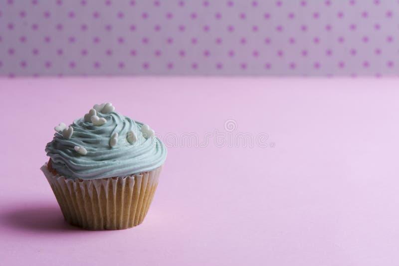 Голубое пирожное с взбитой сливк, и сердце брызгают на розовой точке стоковое изображение
