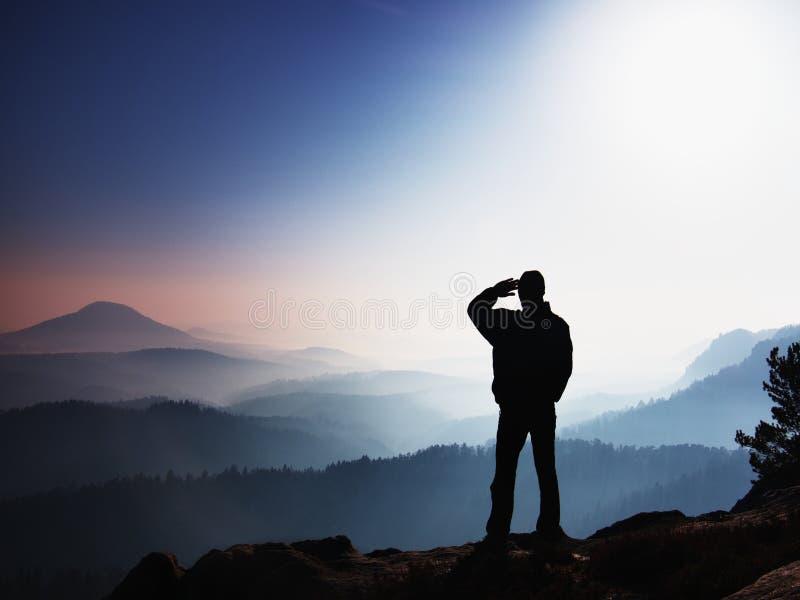 голубое утро Hiker стоит на пике утеса в империях утеса паркует и наблюдает над туманным ландшафтом стоковые фотографии rf