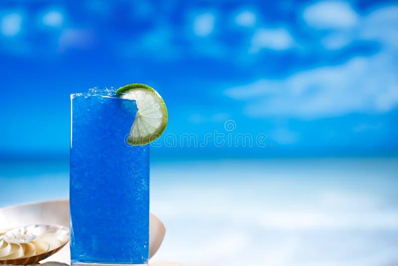 Голубой лед слякоти в стекле на предпосылке пляжа моря стоковые изображения rf