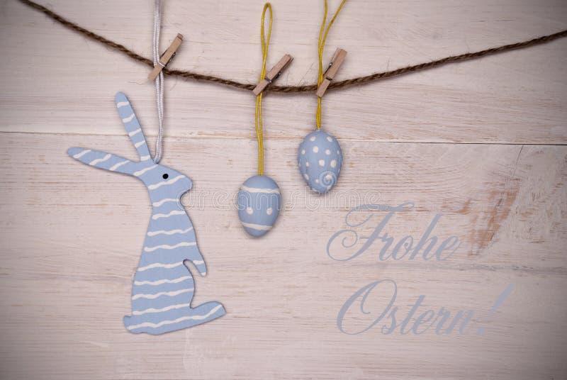 Голубой зайчик пасхи и пасхальные яйца вися на линии с немецкой счастливой пасхой стоковые изображения rf