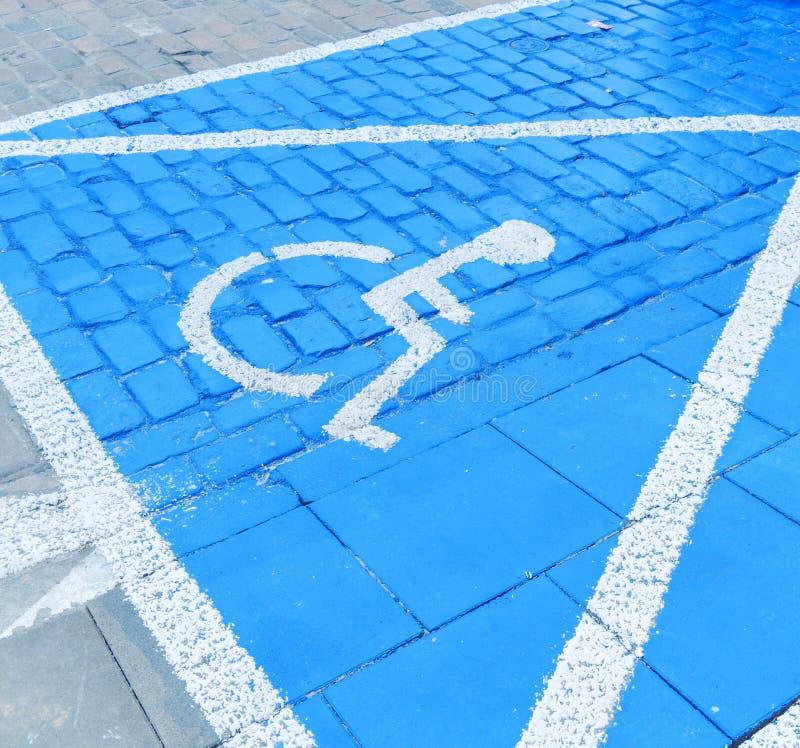Голубой знак автостоянки гандикапа на асфальте для людей с инвалидностью стоковое фото rf