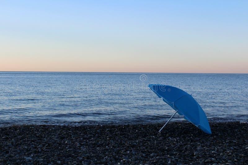 Голубой зонтик на пляже Конец купая сезона стоковая фотография