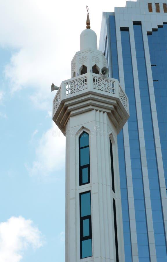 Голубой и белый исламский минарет и современный небоскреб стоковая фотография