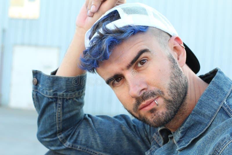 Голубой с волосами прокалыванный ультрамодный мужчина нося бейсбольную кепку стоковое изображение rf