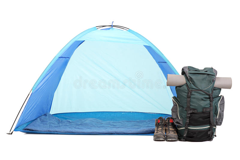 Голубой шатер, рюкзак и пары ботинок на белизне стоковое изображение