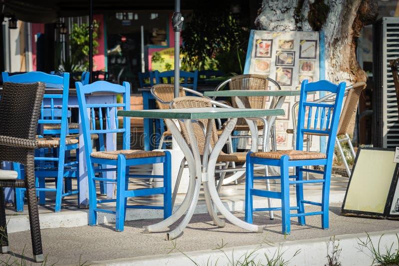 Голубые деревянные стулья и таблица на традиционной греческой харчевне стоковые фотографии rf