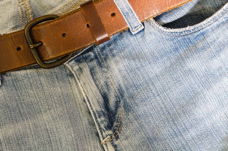 Голубые джинсы и кожаный пояс стоковая фотография rf
