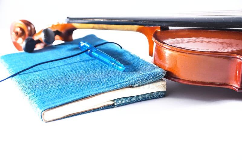 Голубые примечание и скрипка ручки на белой поверхности стоковое фото rf