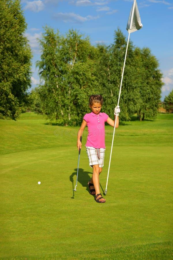 Гольф, игрок в гольф девушки с ручкой и флаг на зеленом цвете стоковая фотография rf