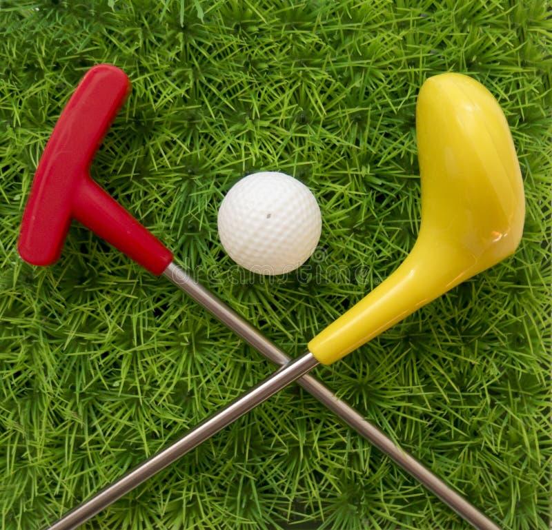 Гольф-клуб игрушки с шариком на траве стоковое фото