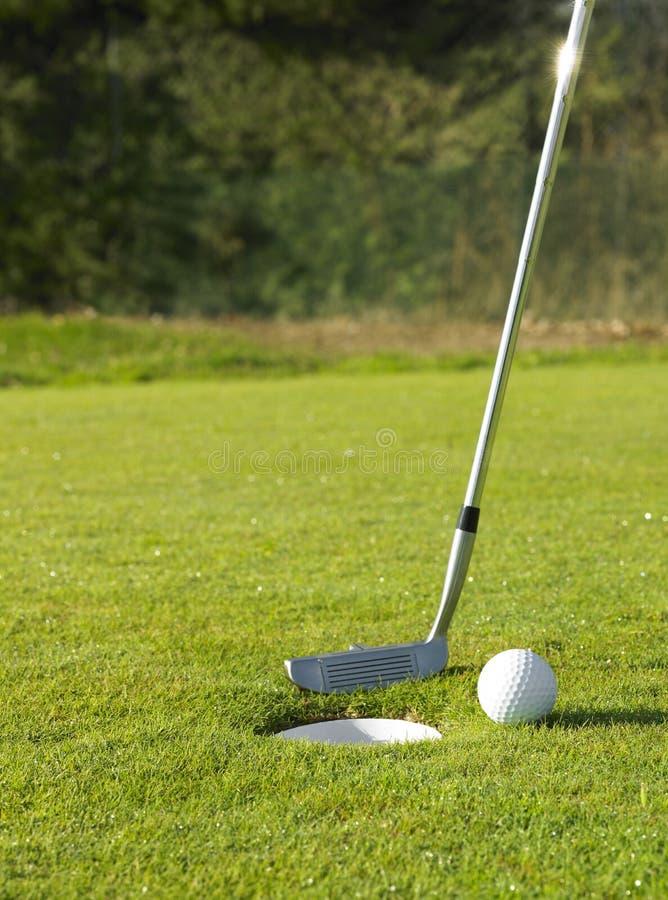 Гольф-клуб и шарик около отверстия стоковые изображения rf