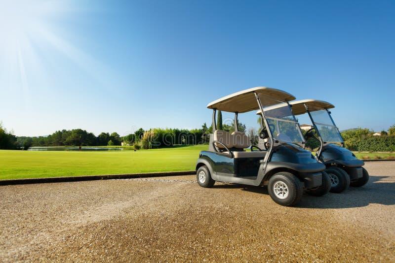2 гольф-тележки стоя на автостоянке в лете стоковые фотографии rf