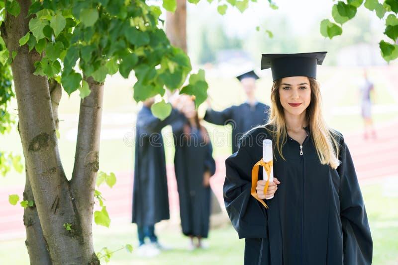 Градация: Студент стоя с дипломом с друзьями позади стоковое изображение rf