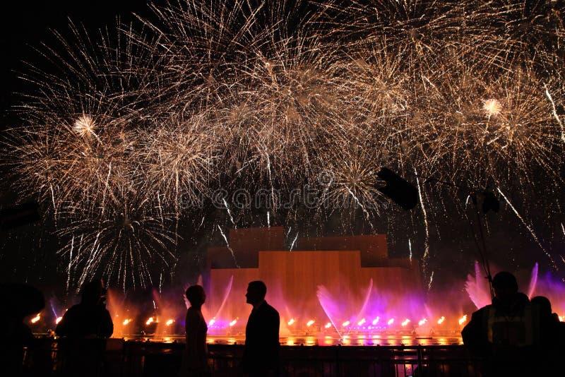 Грандиозные фейерверки и выставка лазера с силуэтами стоковое изображение