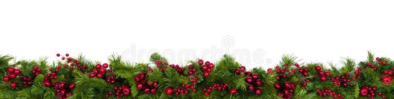 Граница гирлянды рождества с красными ягодами над белизной стоковое изображение rf