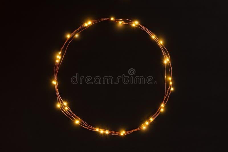 Граница гирлянды светов рождества круговая над черной предпосылкой Плоское положение, космос экземпляра стоковые изображения