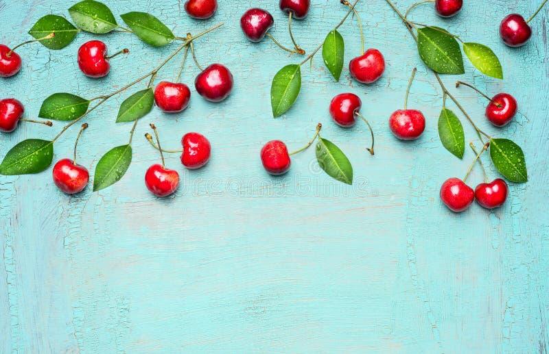 Граница сладостных вишен на ветви с зеленым цветом выходит на свет - голубую предпосылку, взгляд сверху, место для текста стоковое изображение rf