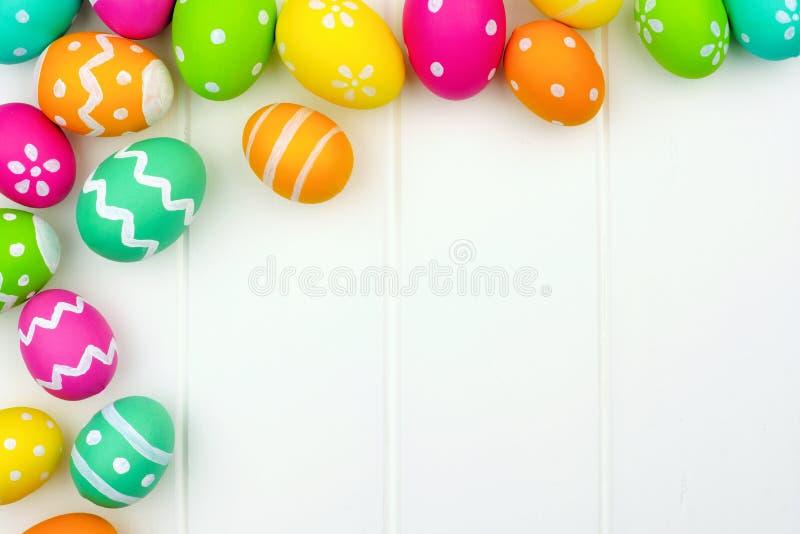 Граница угла пасхального яйца над белой древесиной стоковые фото