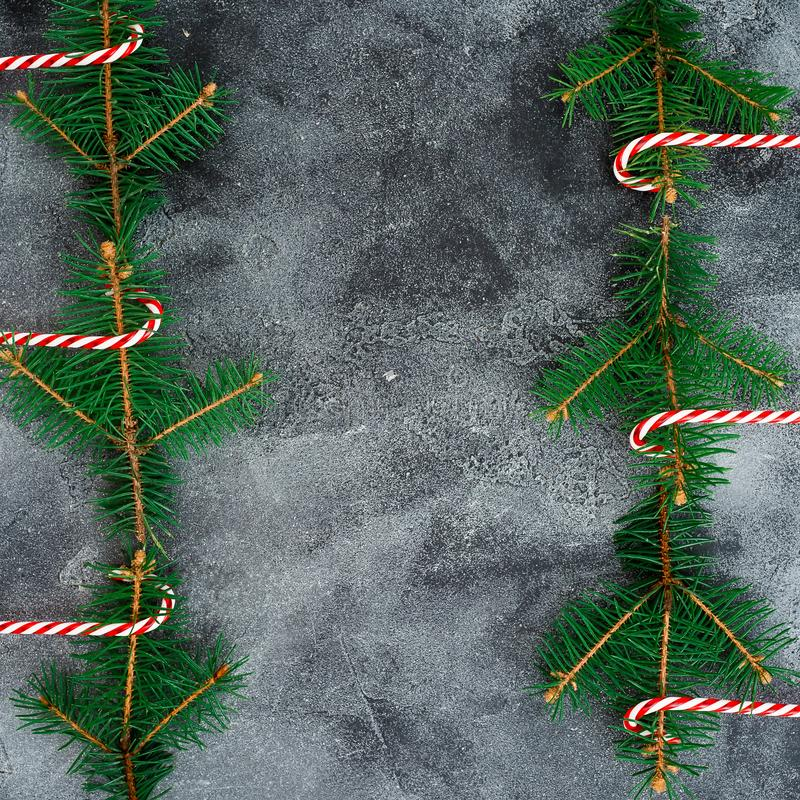 Граничьте рамку сделанную из дерева зимы и тросточки конфеты на серой предпосылке Плоское положение Взгляд сверху Концепция рожде стоковое изображение
