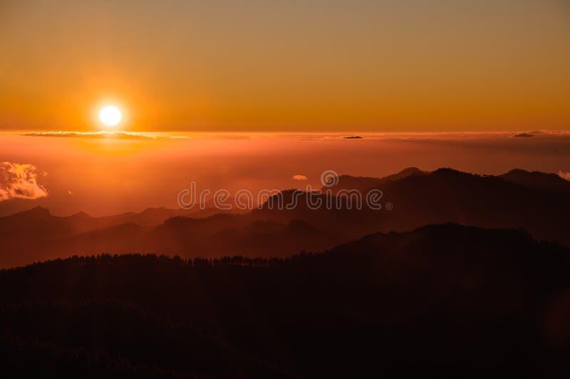 ГРАН-КАНАРИИ, ИСПАНИЯ - 6-ОЕ НОЯБРЯ 2018: Красочный спуск от горы Roque Nublo под небом в ярком оранжевом тумане стоковые фото