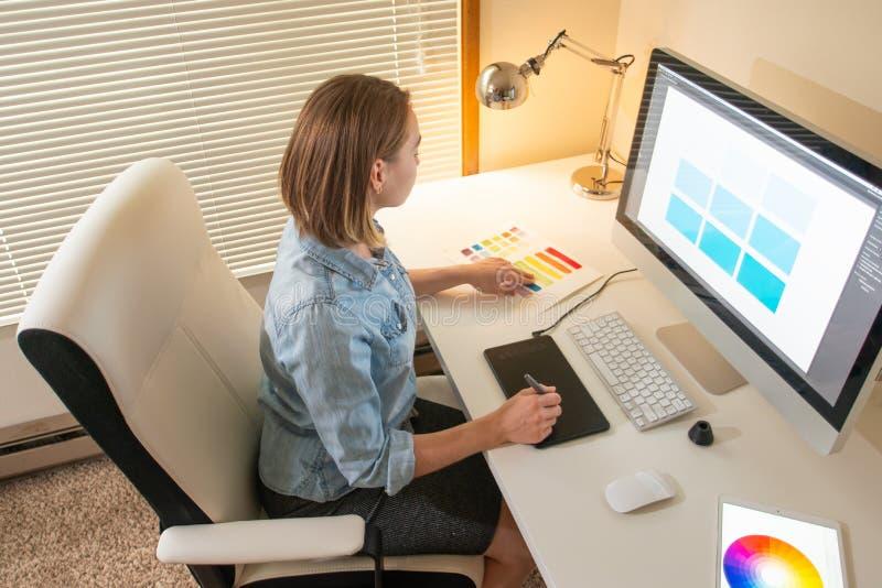График-дизайнер сидя на работе Иллюстратор дизайнер сети freelancer стоковое фото