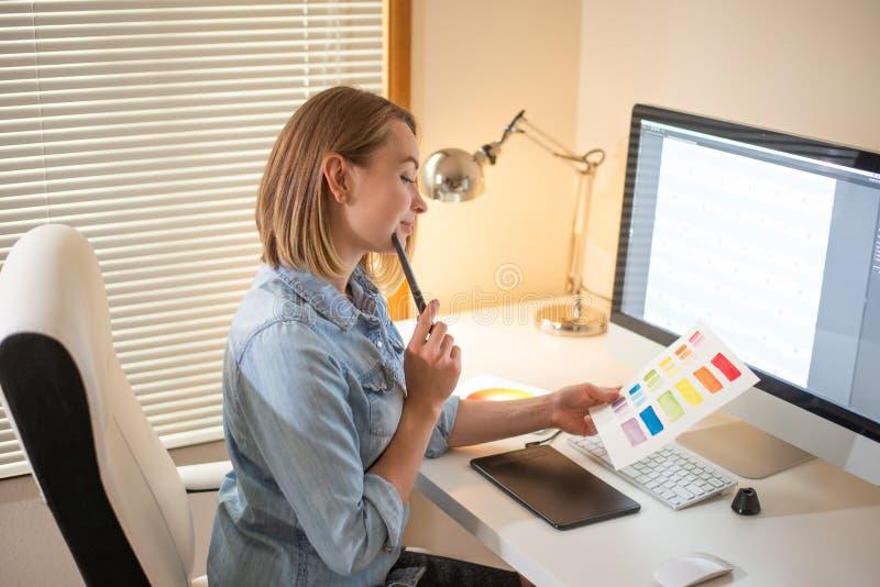 График-дизайнер сидя на работе Иллюстратор дизайнер сети freelancer стоковые изображения