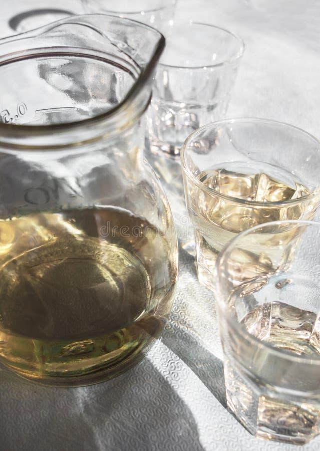 Графинчик и стекла заполненные с домодельным белым греческим вином, на таблице в харчевне в солнечном свете и с красивыми тенями стоковые фотографии rf