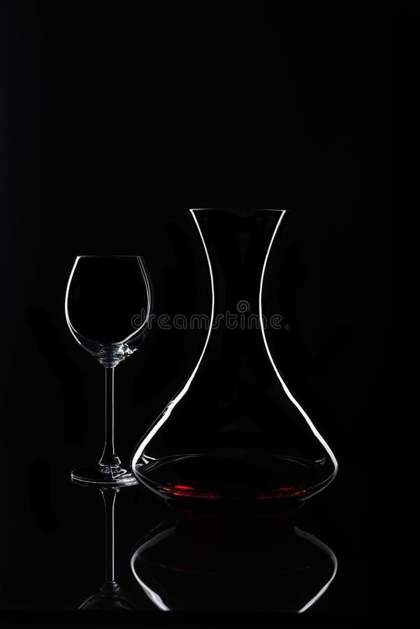 Графинчик с красным вином и стеклом на черной предпосылке стоковые фото