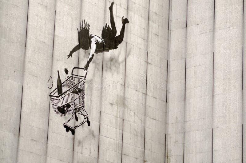 Граффити покупателя Banksy падая, Лондон стоковое изображение