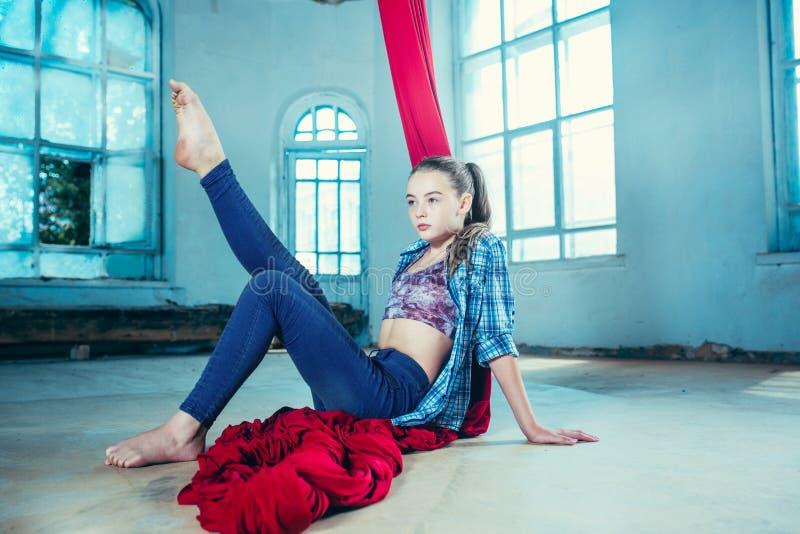 Грациозно гимнаст отдыхая после выполнять воздушную тренировку на просторной квартире стоковая фотография