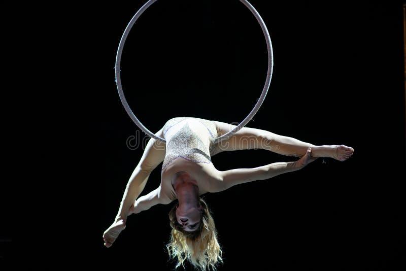 Грациозный воздушный акробат делая ее представление с обручем изолированным на черноте стоковые фото