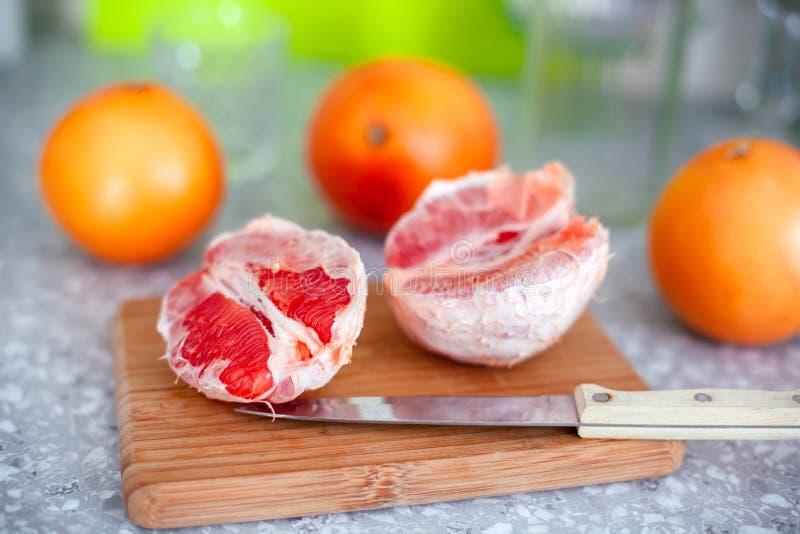 Грейпфруты и нож на разделочной доске стоковые фотографии rf
