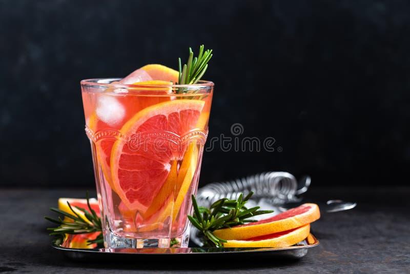 Грейпфрут и свежее розмариновое масло ловят коктеиль в западню с соком, холодным освежающим напитком цитруса лета или напитком с  стоковое фото rf