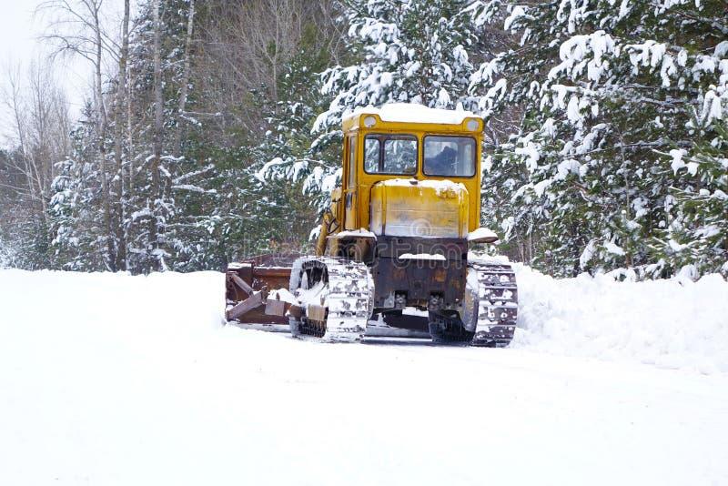 Грейдер трактора Crawler очищает снег на дороге леса стоковое фото