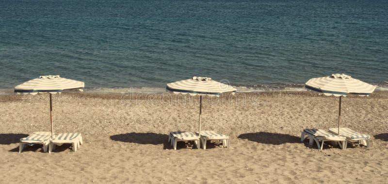 Греция зонтики померанца kos kefalos острова Греции стулов пляжа Стулья и зонтики на пляже Kefalos I стоковые фотографии rf