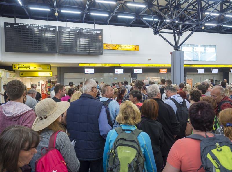 Греция, Корфу, городок Kerkyra, 29-ое сентября 2018: Люди ждать в длинном qeue на счетчике регистрации в аэропорте Корфу, большом стоковые фотографии rf