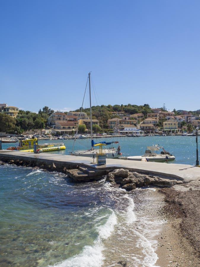 Греция, Корфу, Kassiopi 28-ое сентября 2018: Взгляд набережной и гавани со шлюпкой на Kassiopi, туристской деревне на севере стоковое изображение
