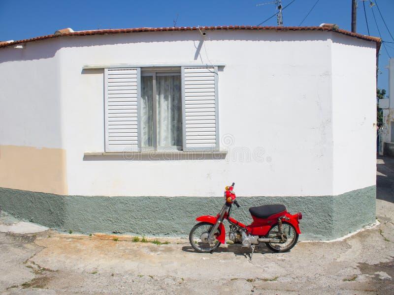 Греция, Родос, апрель 2019 Красный мотоцикл рядом с традиционным белым домом в деревне стоковые фотографии rf