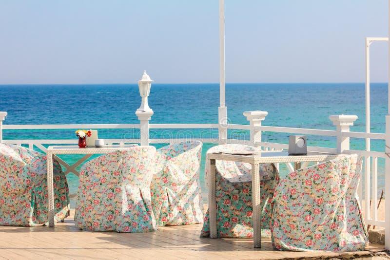 Греция, Santorini Ресторан с, который служат таблицей в набережной Эгейского моря на острове Santorini Кикладов стоковые изображения