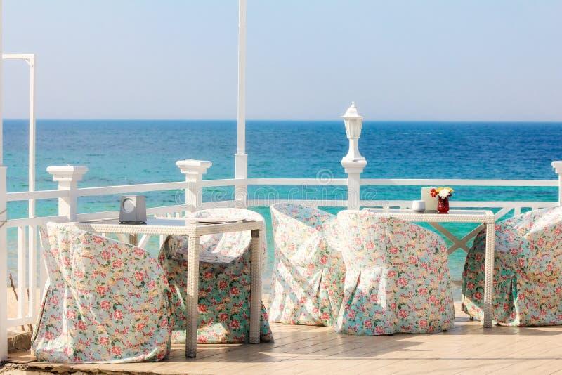 Греция, Santorini Ресторан с, который служат таблицей в набережной Эгейского моря на острове Santorini Кикладов с захватывающим стоковая фотография
