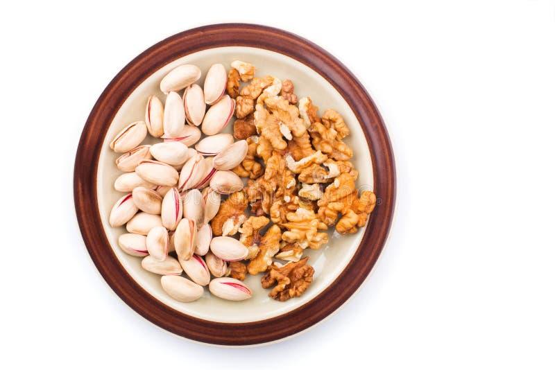 Грецкие орехи и фисташки в коричневой плите Изолированный на белом backg стоковая фотография rf