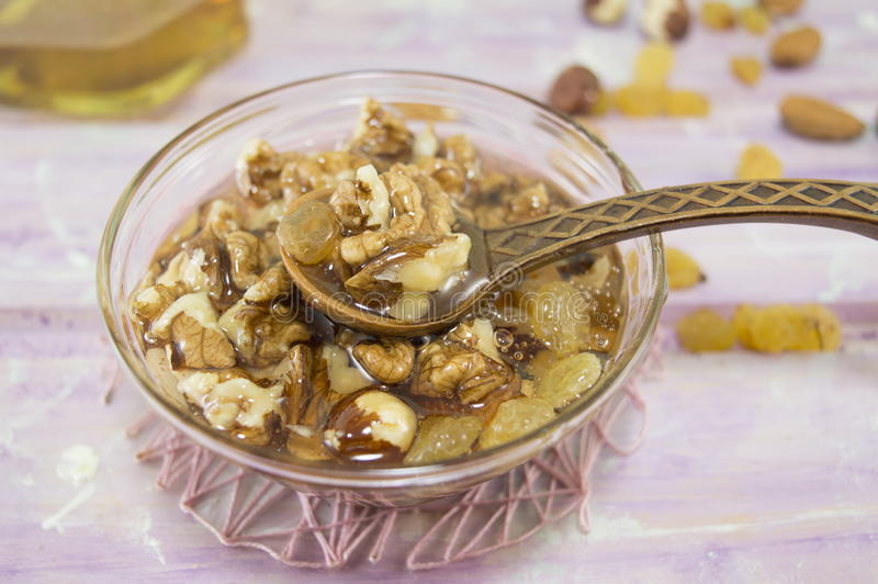 Грецкие орехи, фундуки и мед в стеклянном блюде стоковые изображения rf