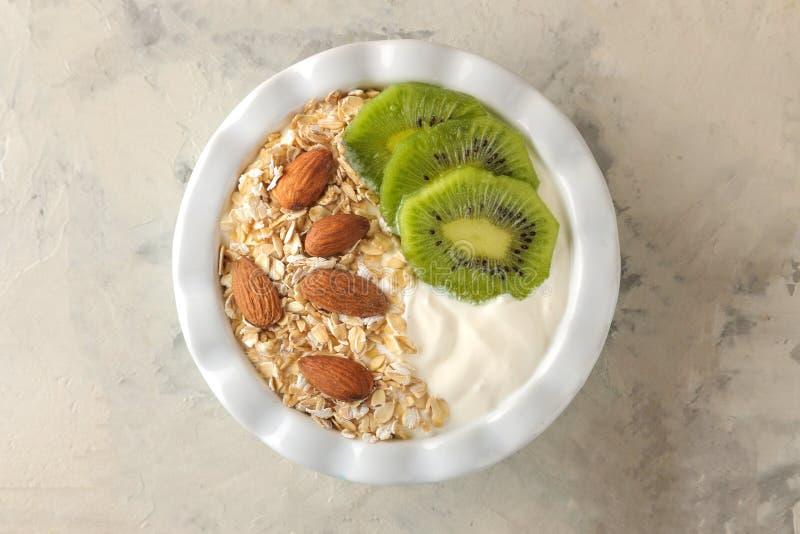 Греческий белый йогурт с миндалинами и овсяной кашей кивиа на светлой конкретной таблице взгляд сверху завтрака E стоковые изображения rf