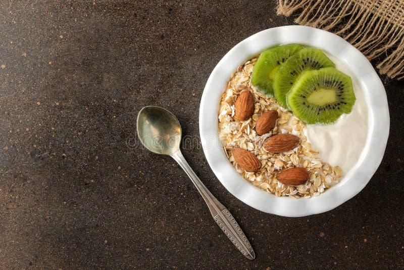 Греческий белый йогурт с миндалинами и овсяной кашей кивиа на темной коричневой таблице взгляд сверху завтрака E стоковые фотографии rf