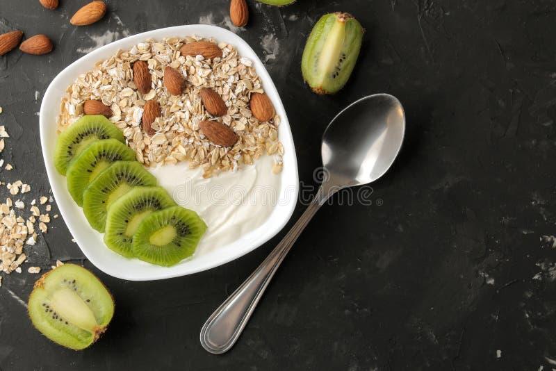 Греческий белый йогурт с миндалинами и овсяной кашей кивиа на темной таблице графита взгляд сверху завтрака E стоковое изображение