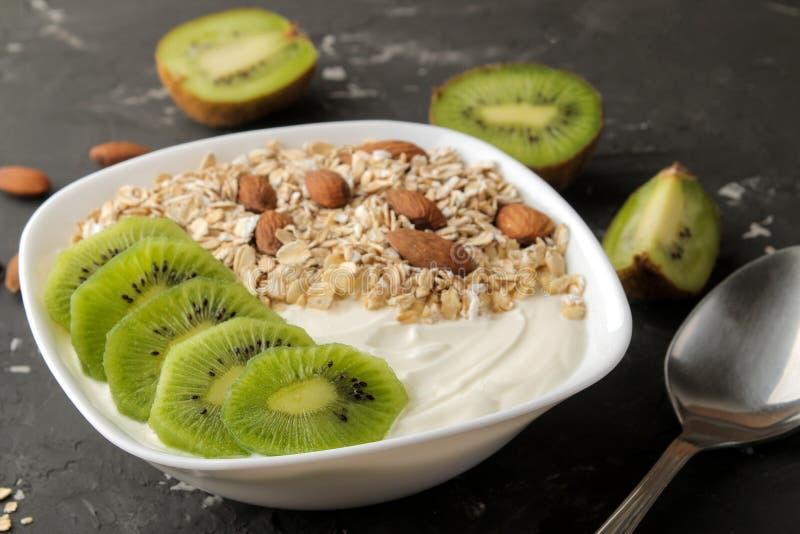 Греческий белый йогурт с миндалинами и овсяной кашей кивиа на темной таблице графита еда завтрака здоровая стоковая фотография rf
