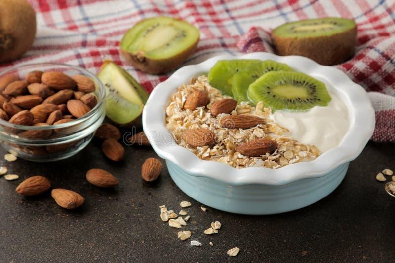 Греческий белый йогурт с миндалинами и овсяной кашей кивиа на темной коричневой таблице еда завтрака здоровая стоковое фото