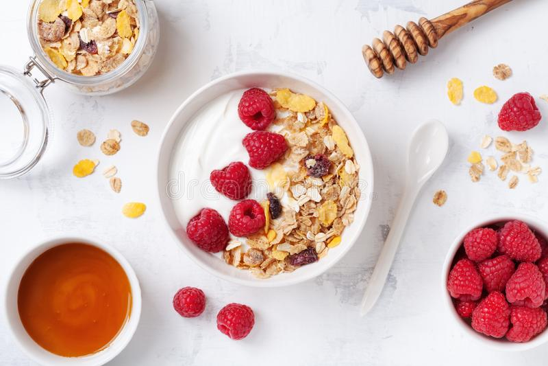Греческий йогурт в шаре с полениками, медом и muesli на белом каменном взгляде столешницы Завтрак здорового питания стоковое изображение rf