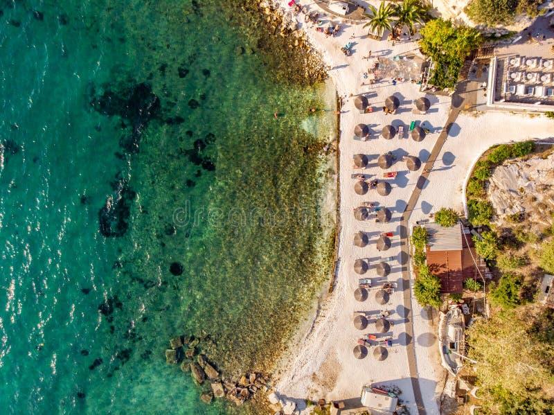 Греческий пляж с песком и ясной верхней частью открытого моря вниз со съемки вида с воздуха используя трутня стоковое фото