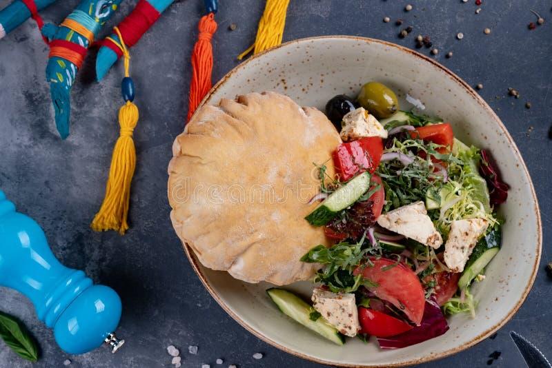Греческий салат со свежими томатами вишни, сыром фета, черными оливками, базиликом и луком на черной каменной предпосылке, блинчи стоковая фотография rf